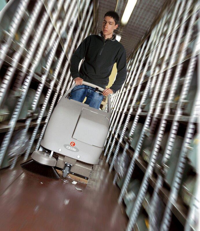 Фото поломоечная машина среди стеллажей. Уборка рабочего прохода