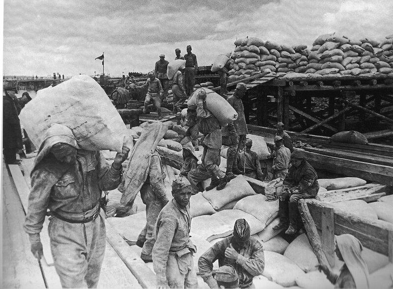 Советские солдаты разгружают баржу с мукой в ладожском порту Осиновец
