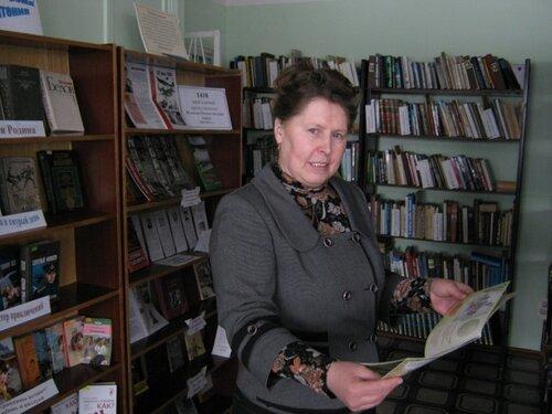 Библиотекарь Елена Николаевна с подаренной библиотеке книжкой.