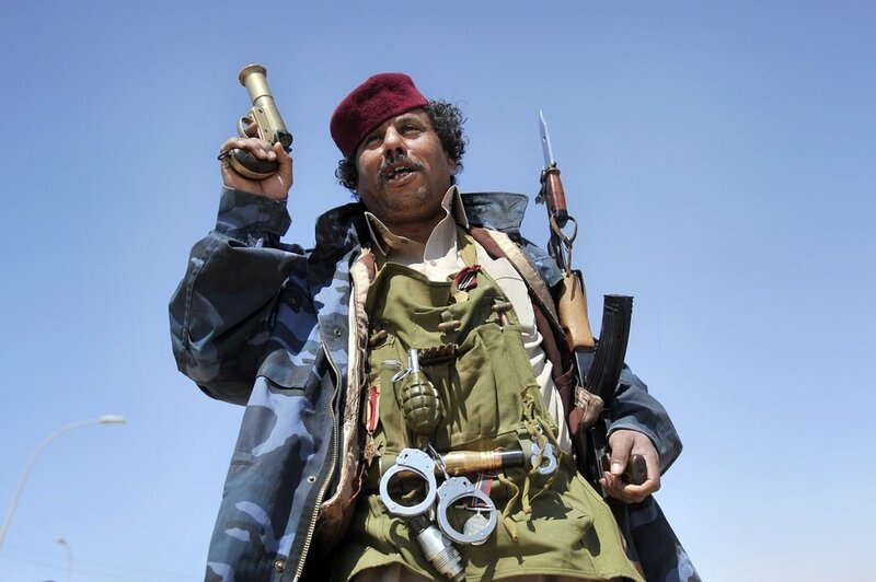 A Libyan rebel poses with his weapons on