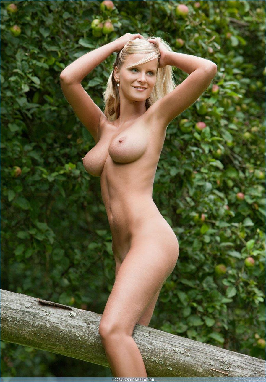 Блондинка с большой грудью позирует у ограды (20 фото)