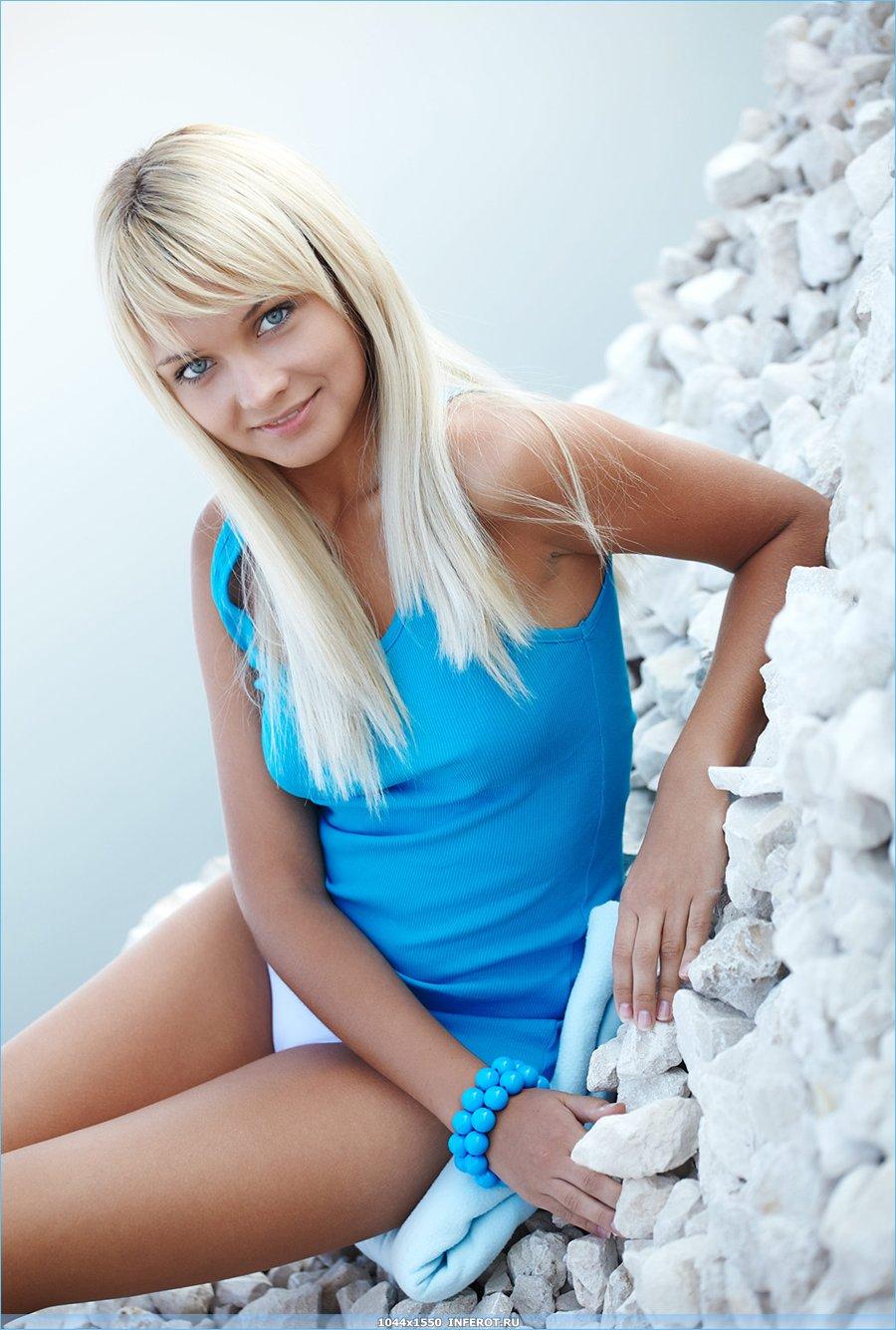 голая блондинка на каменистом берегу