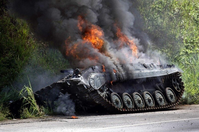 A tank burns by the roadside after heavy fighting in Ivory Coast's main city Abidjan