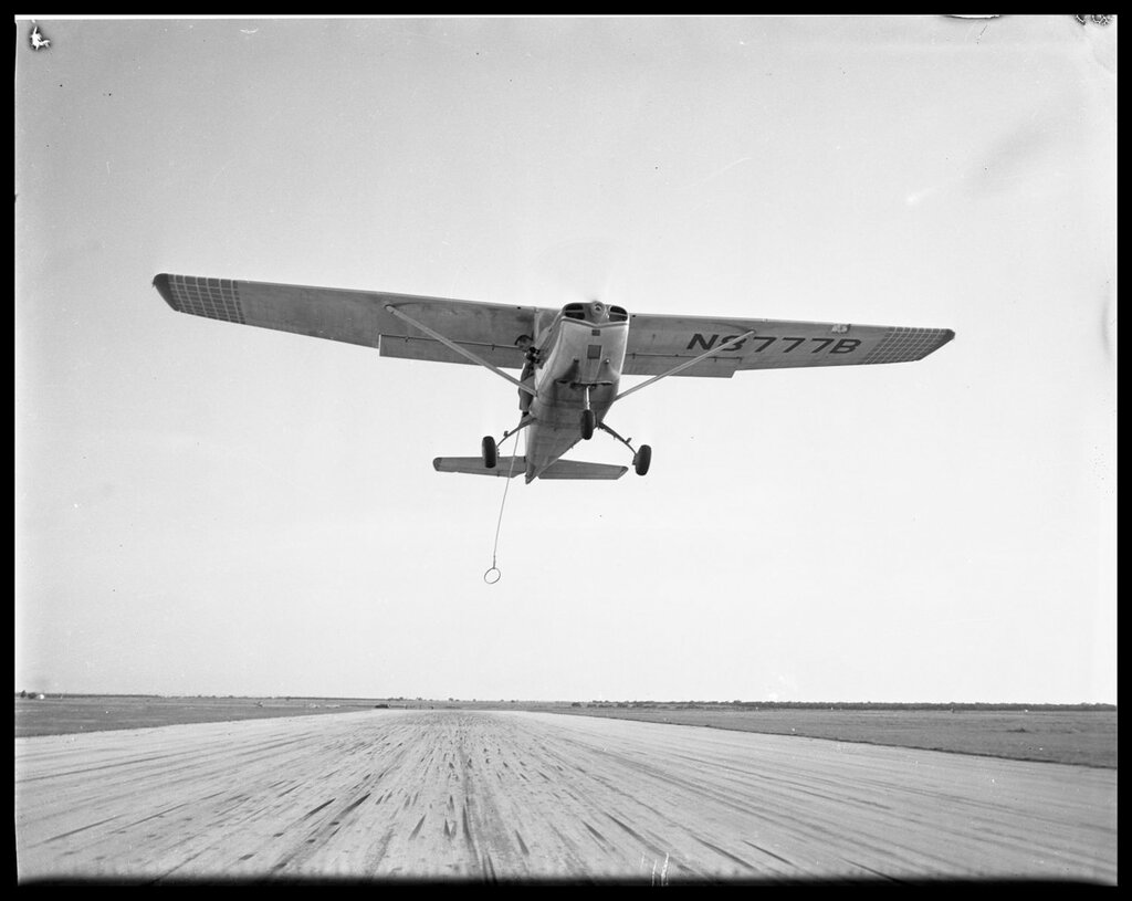 Refueling Airplane N8777B flying above a truck on a runway. Texas - Taylor County - Abilene, 1958