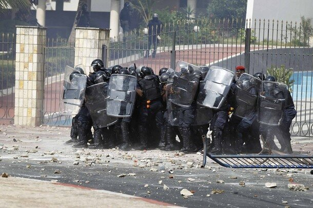 Riot police use their shields against a barrage of stones thrown by protestors in Senegal's captial Dakar