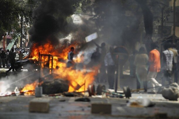 Anti-government protesters walk past a burning vehicle and barricades during a demonstration in the capital Dakar