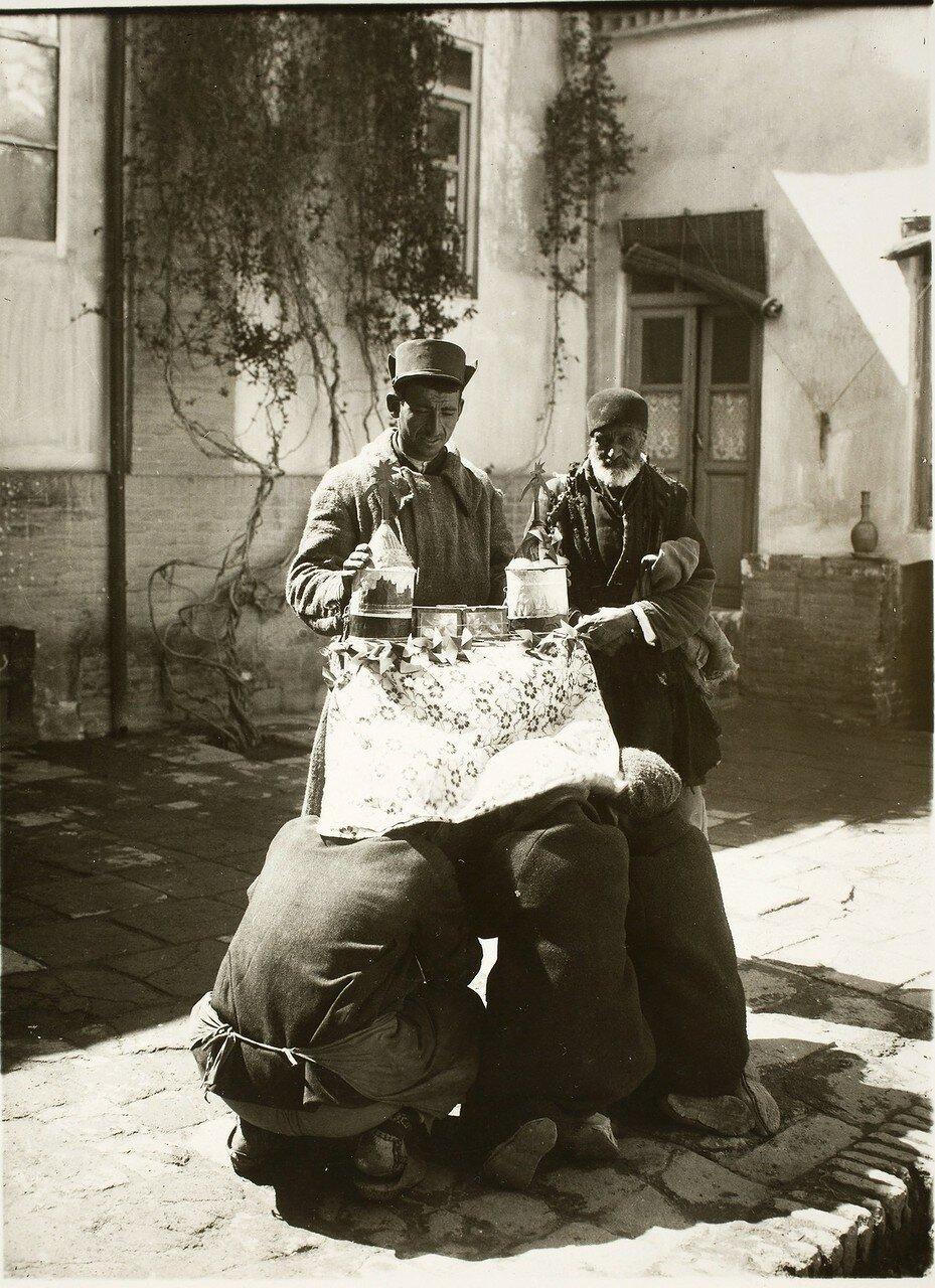 Мужчины смотрят движущиеся изображения в устройстве широко известном как Шахри Фаранг