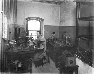 Рабочие за изготовлением частей радиоаппаратуры.