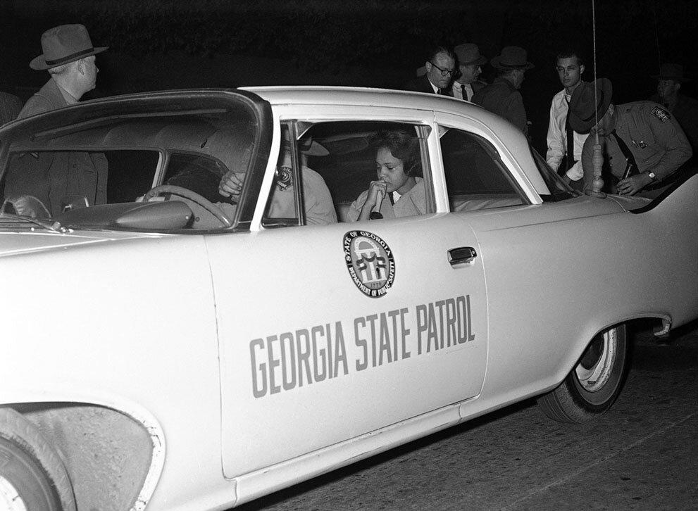 Чернокожая девушка под защитой  полицейских после восстания студентов против интеграции. 12 января 1961 года.