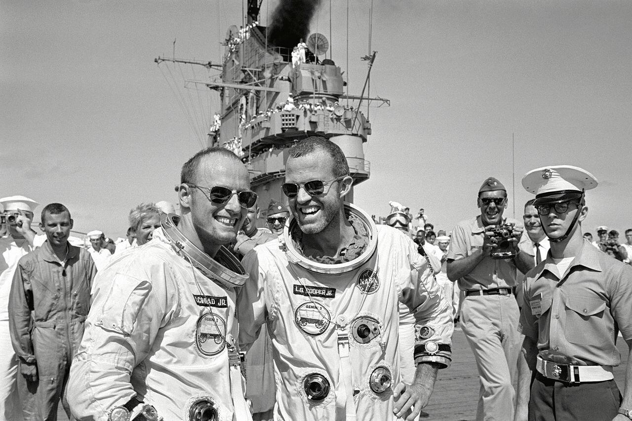 1965, 29 августа. Л. Гордон Купер-младший (справа) и Чарльз Конрад младший ходят по палубе авианосца USS Lake Champlain (CVS-39) после приводнения.