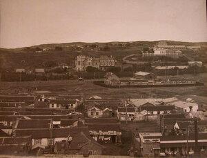 Вид жилых домов (на первом плане) и здания больницы (на втором плане).