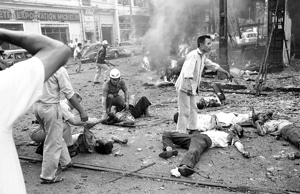 Раненые лежат на улице после взрыва бомбы у здания посольства США в Сайгоне. В результате произошедшего было убито 2 американца и несколько вьетнамцев