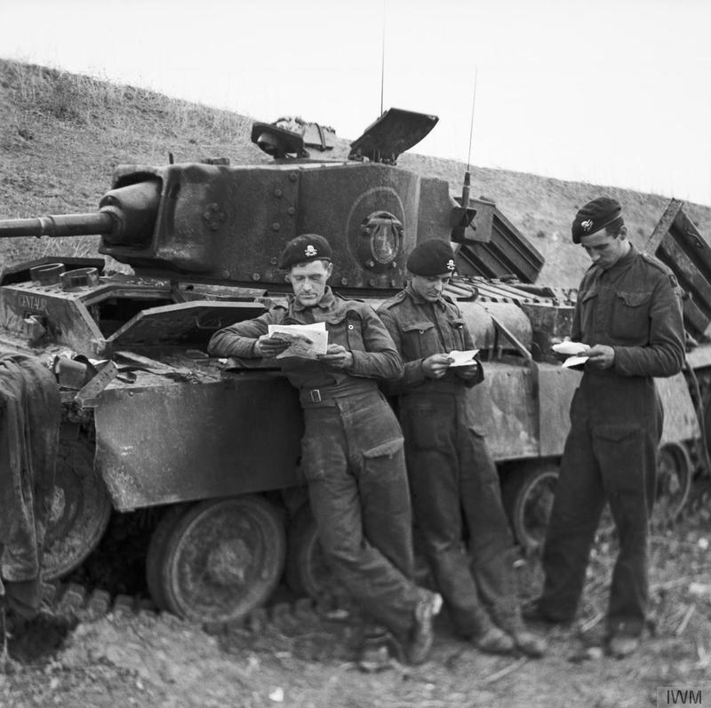 Crew of a Valentine III tank reading their recently arrived mail in Tunisia, after they had come out of action, December 1942