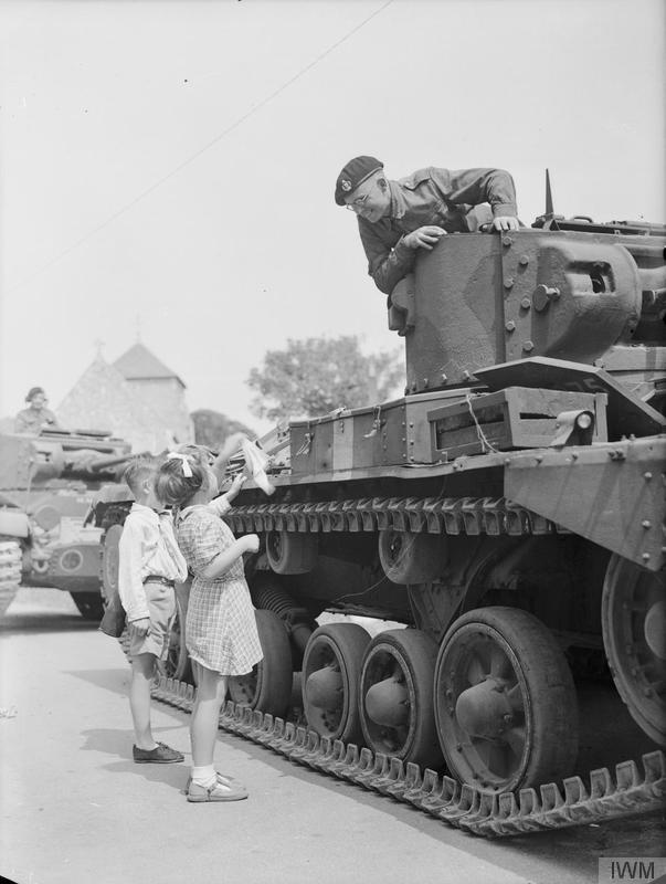 Tank commander Corporal Harry Stephenson leans down from the turret of his Valentine tank of 11th Armoured Division to speak to 5-year-old Pat Brooker in the village of Rottingdean in Sussex, England, 25 June 1942