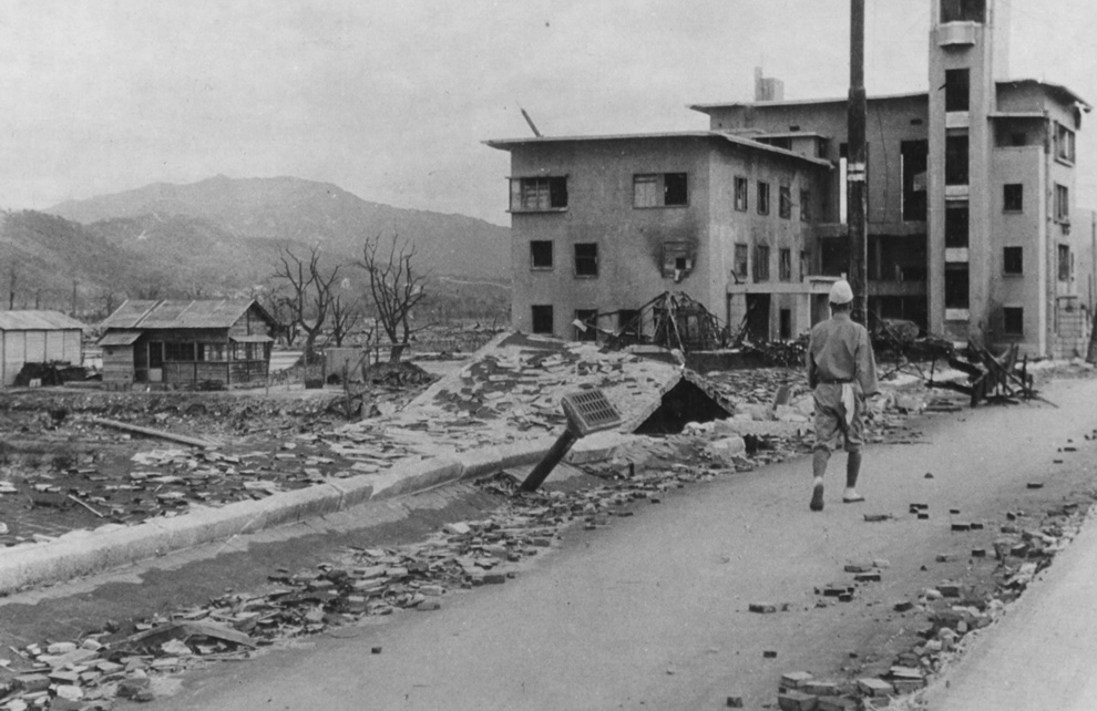 15. Разрушенная улица в Хиросиме. Взгляните, как был приподнят тротуар, а из моста торчит водосточна