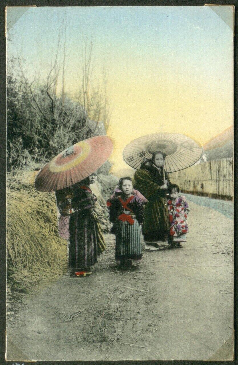 Две женщины с зонтиками и детьми в деревне