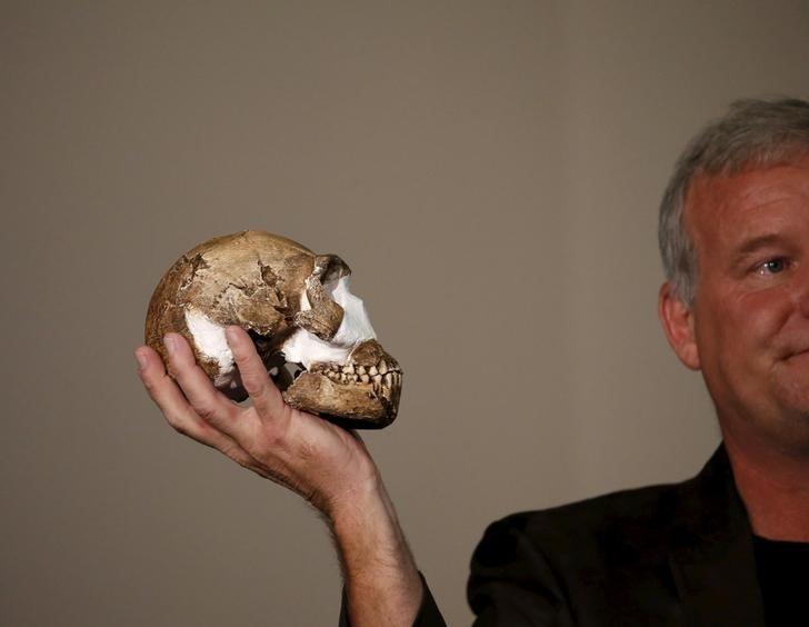 Профессор Ли Бергер держит копию черепа недавно открытых древних человекоподобных существ, названных
