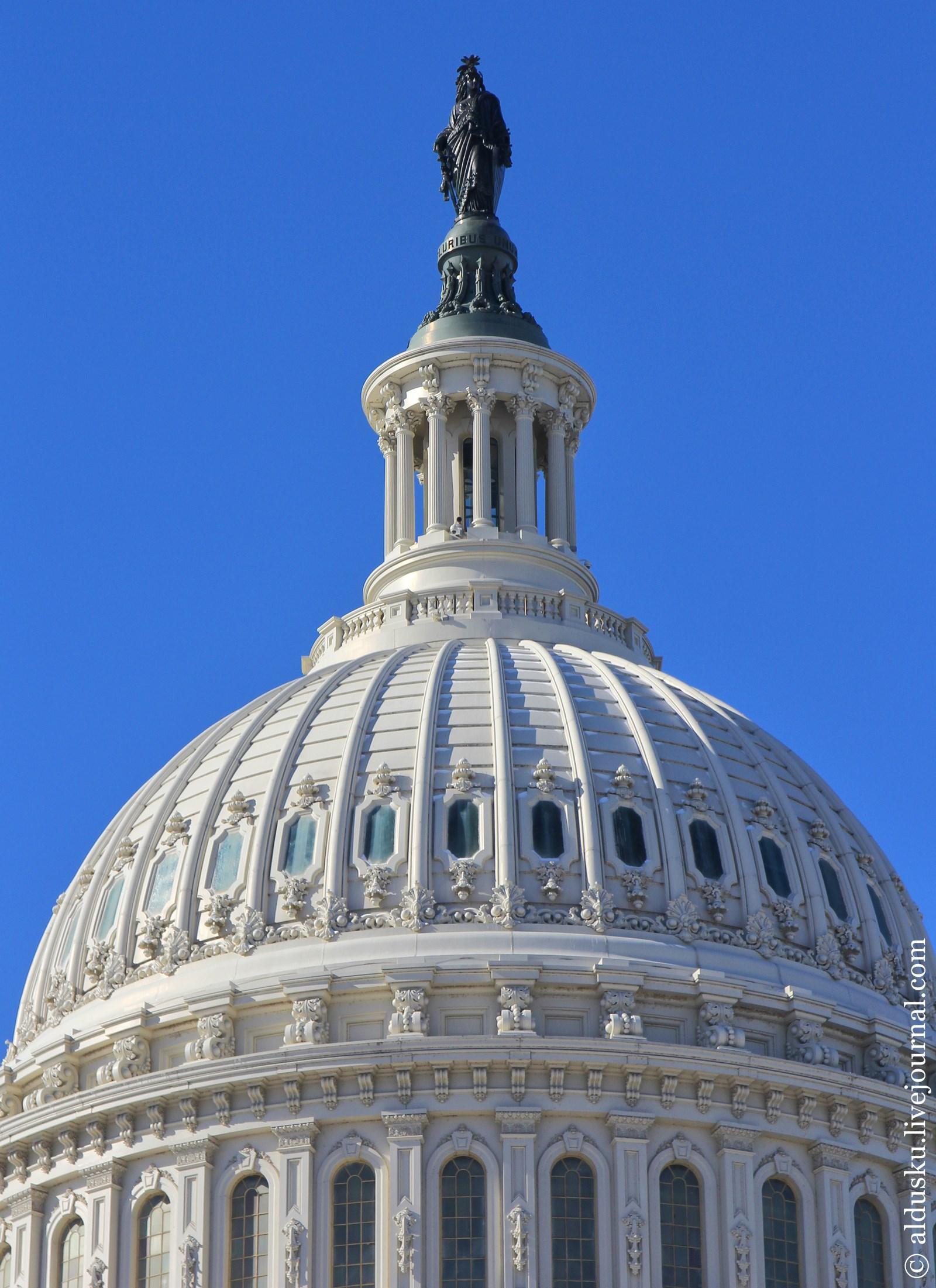 Статуя Вооруженной Свободы выше купола Капитолия имеет на голове венок из пятиконечных звезд, а в руках держит меч и щит.