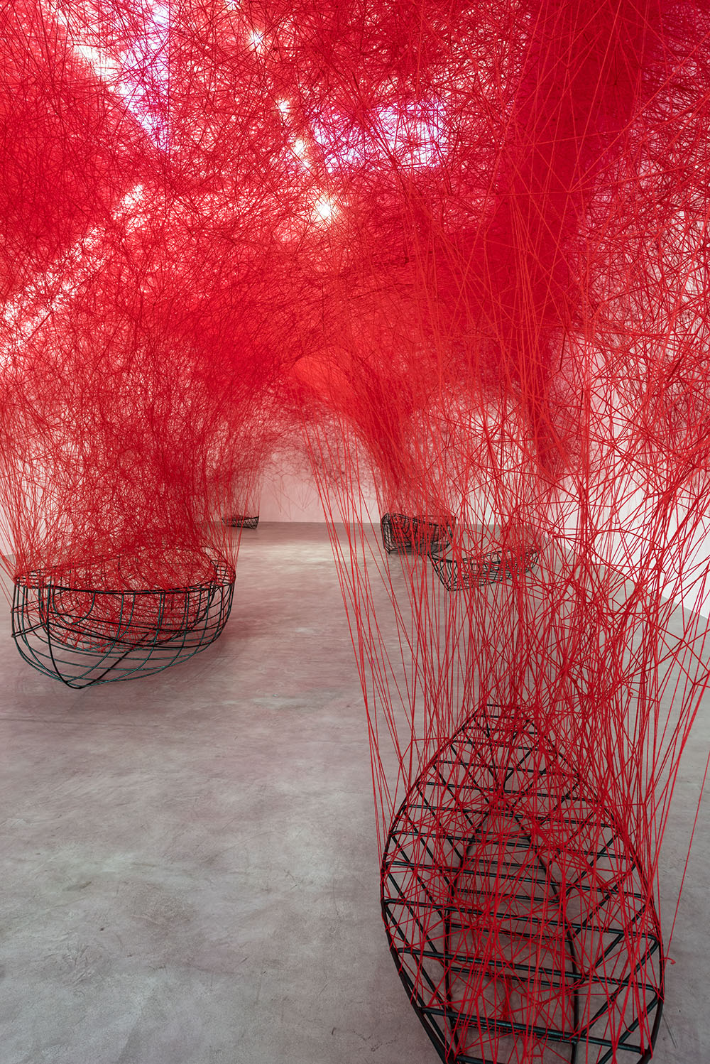 Uncertain Journey: A Flotilla of Wireframe Boats Overflow With a Dense Canopy of Red Yarn
