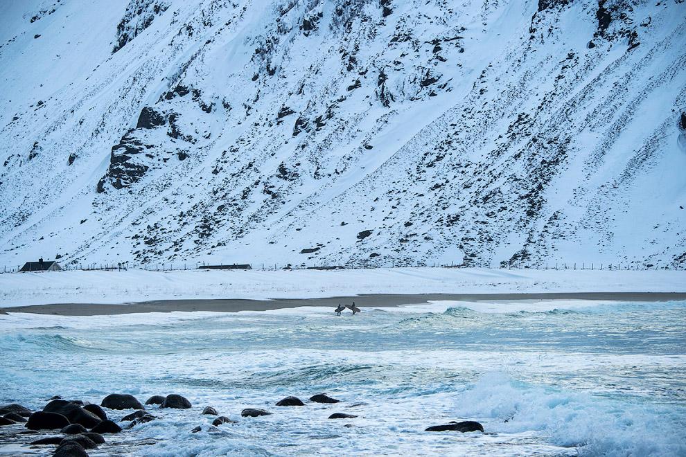 Сёрфер и северное сияние на Лофотенских островах.