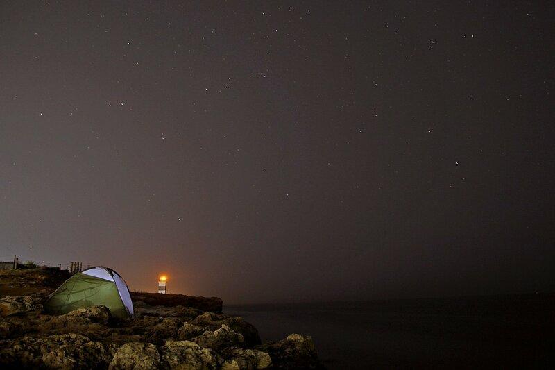 Палатка и маяк на скалистом берегу Чёрного моря ночью среди звёзд (Севастополь, Крым)