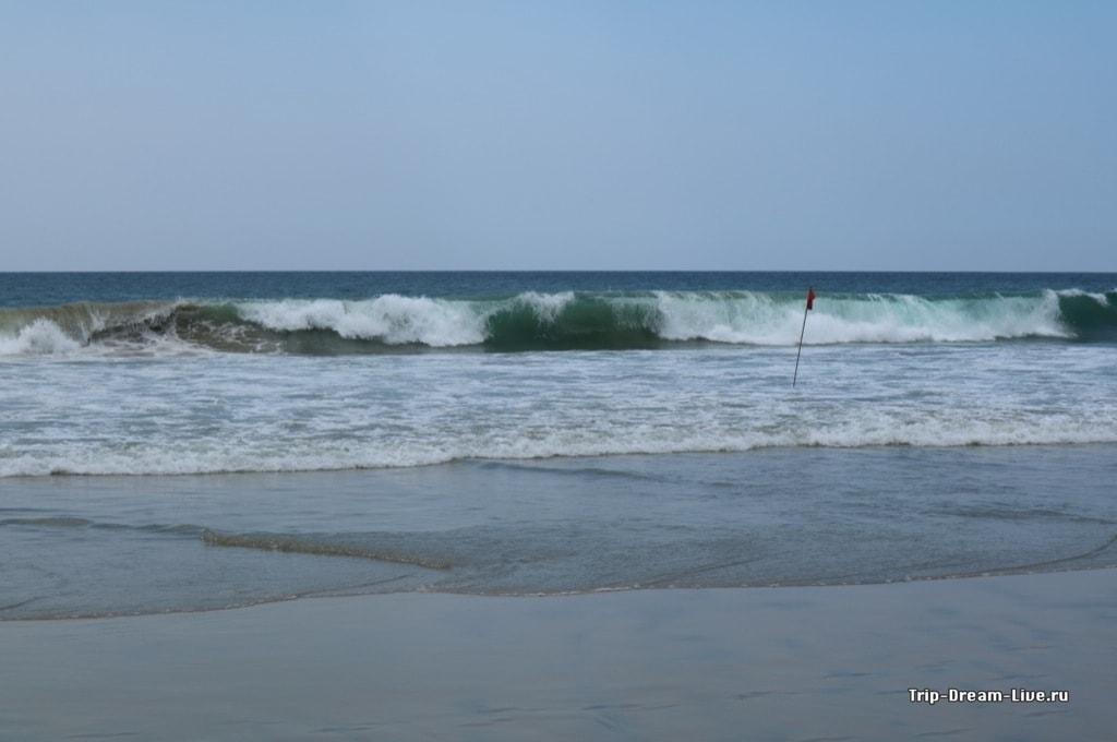 Волны и красные флаги на пляже Лайтхаус