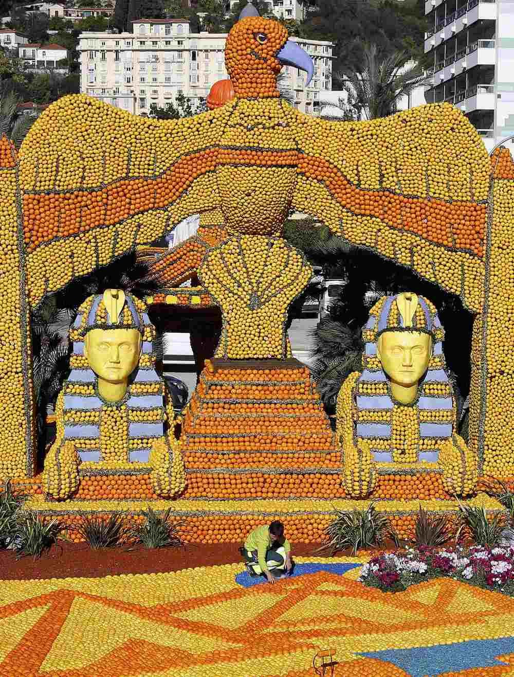 A worker puts the final touch to a replica of a giant eagle and pharaons made with lemons and oranges which shows a scene of the movie