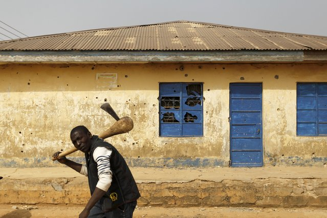 A man carrying an axe walks past a house marked with bullet holes in Gyallesu district after recent