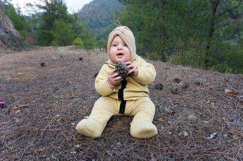 ребенок во флисовом комбинезоне и шапке в походе