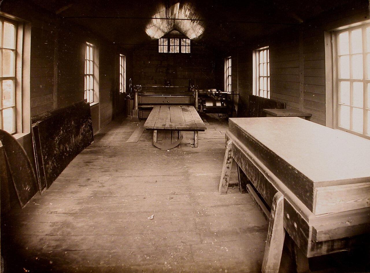 15. Вид части одного из цехов мастерской; на заднем плане – станок