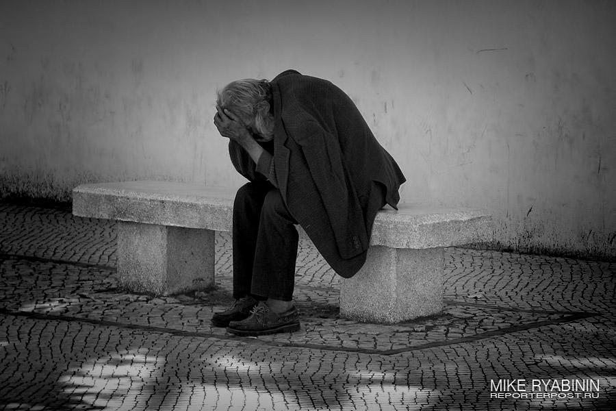 Бездомный спит на лавочке в Порто (Португалия).