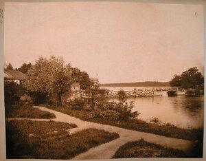 Вид жилых домов на берегу озера в дачной местности Пикруки; справа - мост и плотина.