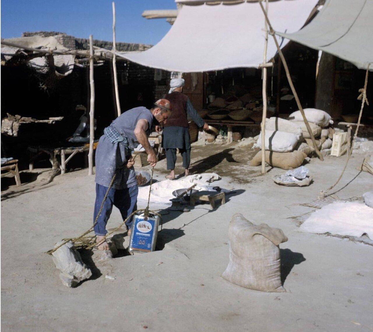 Люди набирают воду из колодца