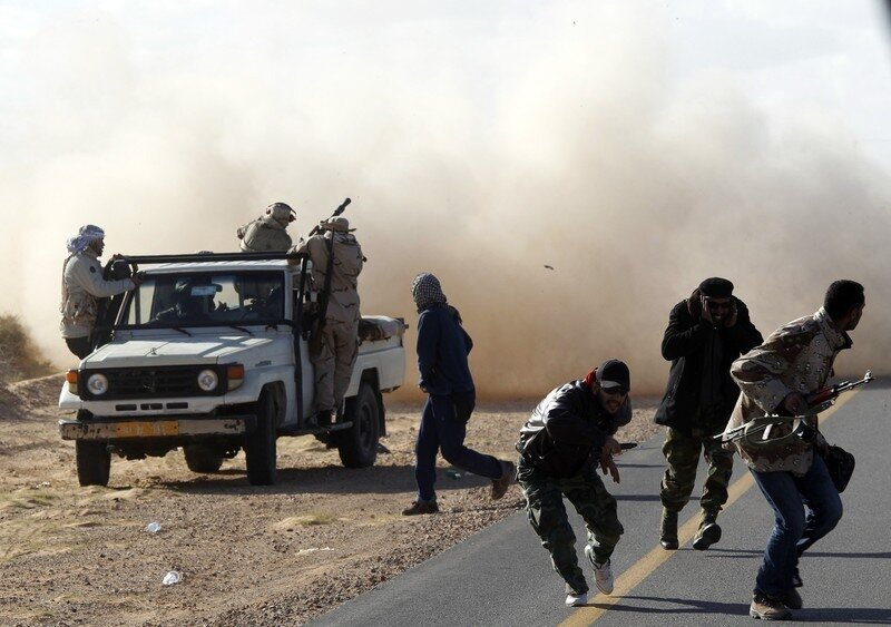 Rebel fighters run for cover during heavy shelling by forces loyal to Libyan leader Muammar Gaddafi near Bin Jawad