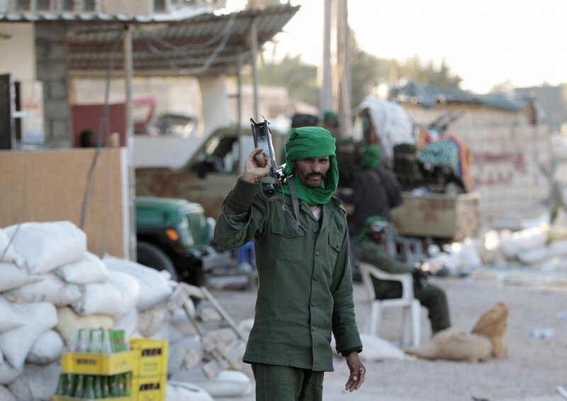A Libyan soldier loyal to leader Muammar Gaddafi stands in a street strewn with rubble in the city of Misrata