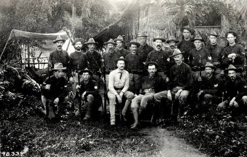 Officers and non-commisioned officers of Company E, 30th Volunteer Infantry Regiment seated outside a native Nipa Hut, who served in the Philippine Islands from October, 1899 until February 101. During this time they partisipated in actions in the Manil