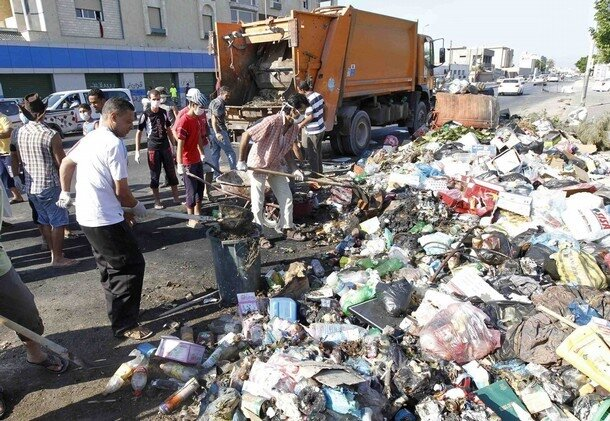 Libyan citizens clear garbage along a street in Tripoli