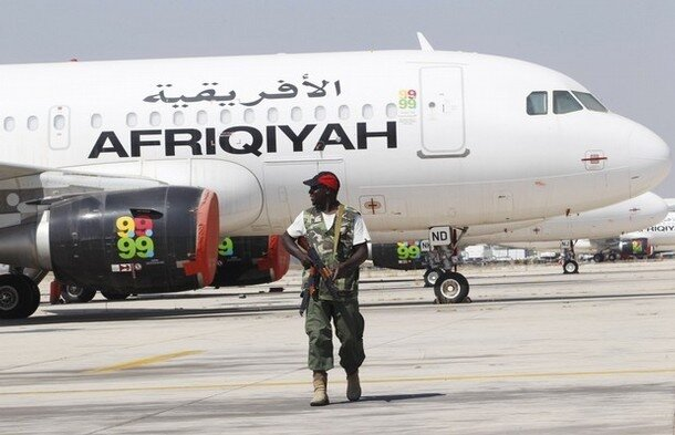 A rebel fighter takes up position at Tripoli Airport