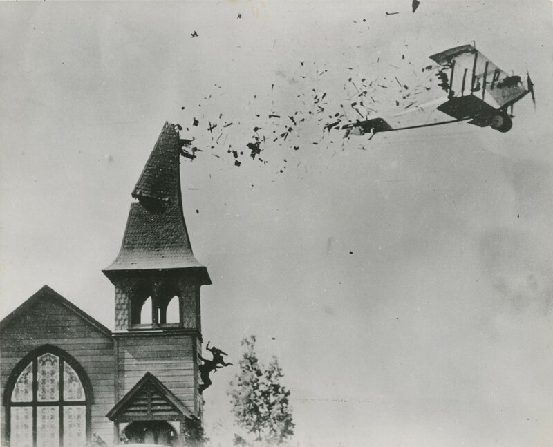 """Crash their Curtiss """"Jenny"""" into the break-away steeple of the First Baptist Church in Sunland for a scene in Willian Fox's The Skywayman. 1920"""