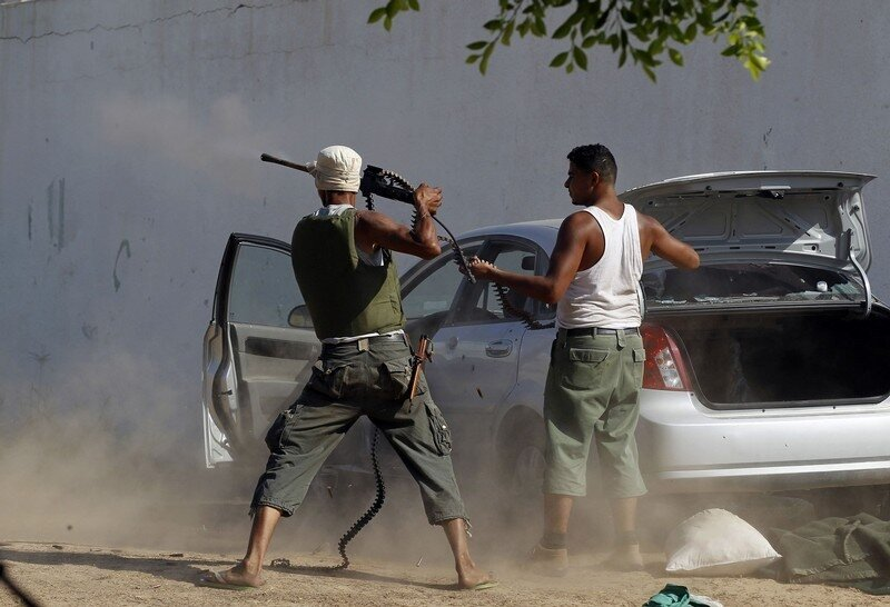 A Libyan rebel fighter fires his machine gun toward a sniper as they make a final push to flush out pro-Gaddafi forces in Tripoli
