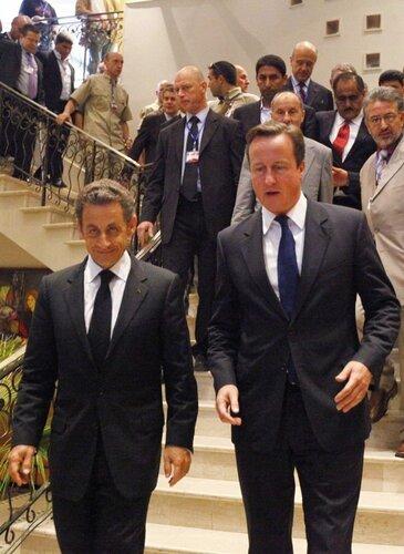 France's President Nicolas Sarkozy and Britain's Prime Minister David Cameron walk together in Tripoli