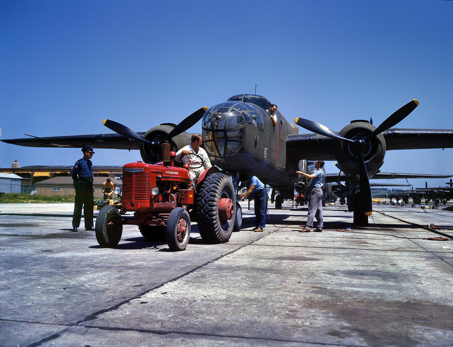 "October 1942. Kansas City, Kansas. ""B-25 bomber plane at North American Aviation being hauled along an outdoor assembly line."".jpg"
