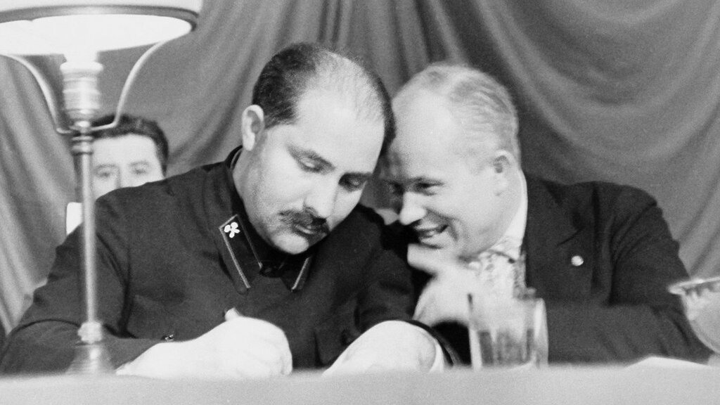 Л. М. Каганович (слева) и Н. С. Хрущев в президиуме собрания по поводу открытия прожекторного завода в Москве в 1935 году.jpg