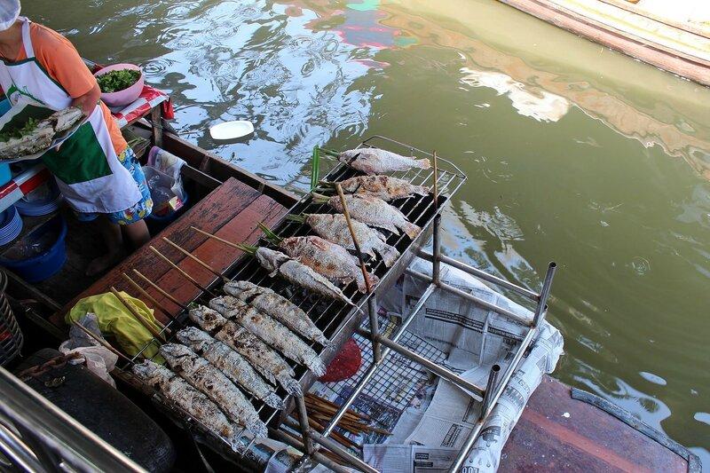 Готовится рыба на гриле на лодке в канале у плавучего рынка Талинг Чан, Бангкок, Таиланд