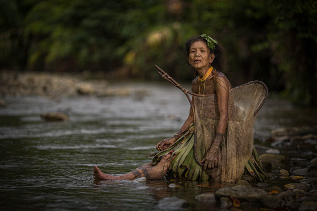 Woman of the tribe wear traditional handmade skirts to catch fish in the local river taken on July 1