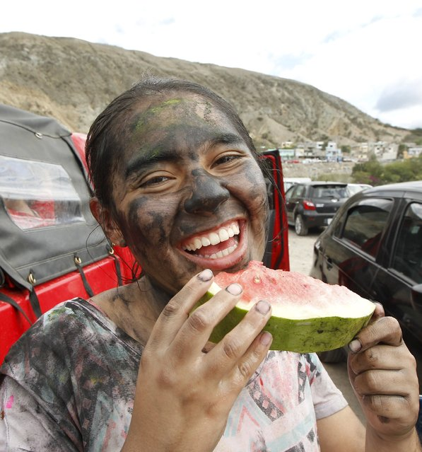 A reveller enjoys a watermelon slice at the Chota river during a carnival celebration in Coangue, Fe