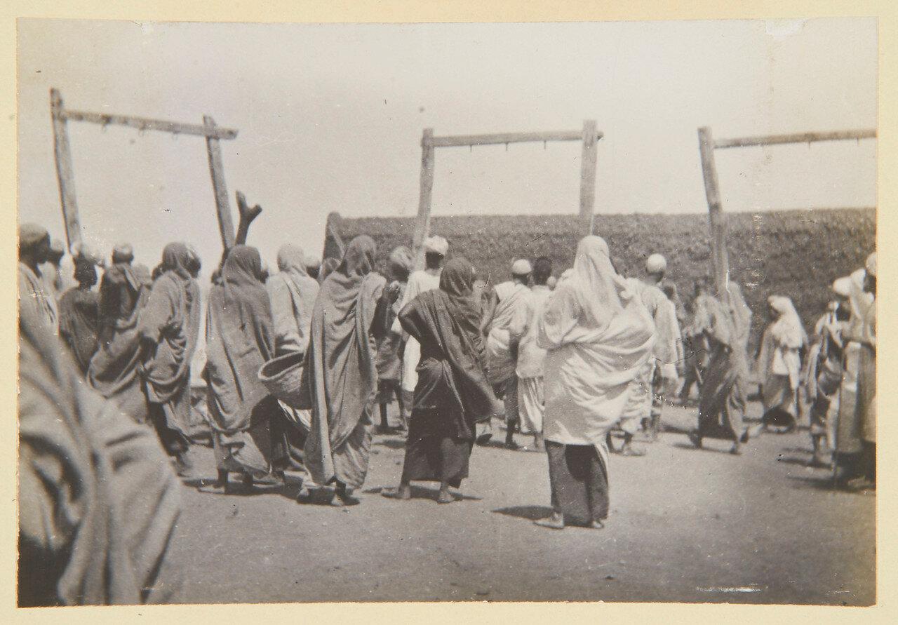 Толпа вокруг тела человека, последнего из повешенных по приказу Халифа