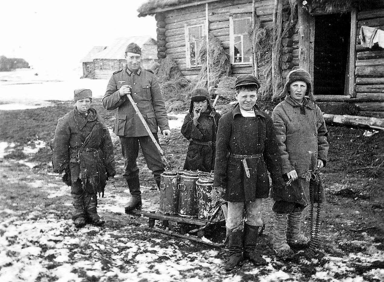 Немецкий солдат с местными ребятами.