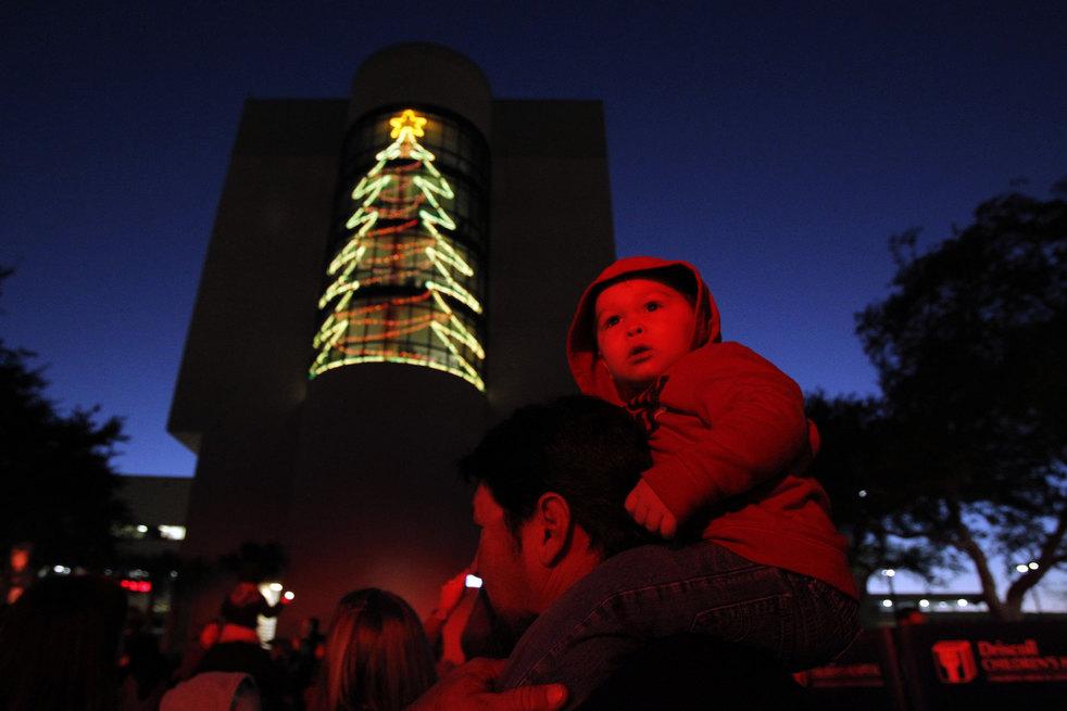 28. 20-месячный Эмиль Бэйкер-младший смотрит на праздничные гирлянды и огни на территории детской бо