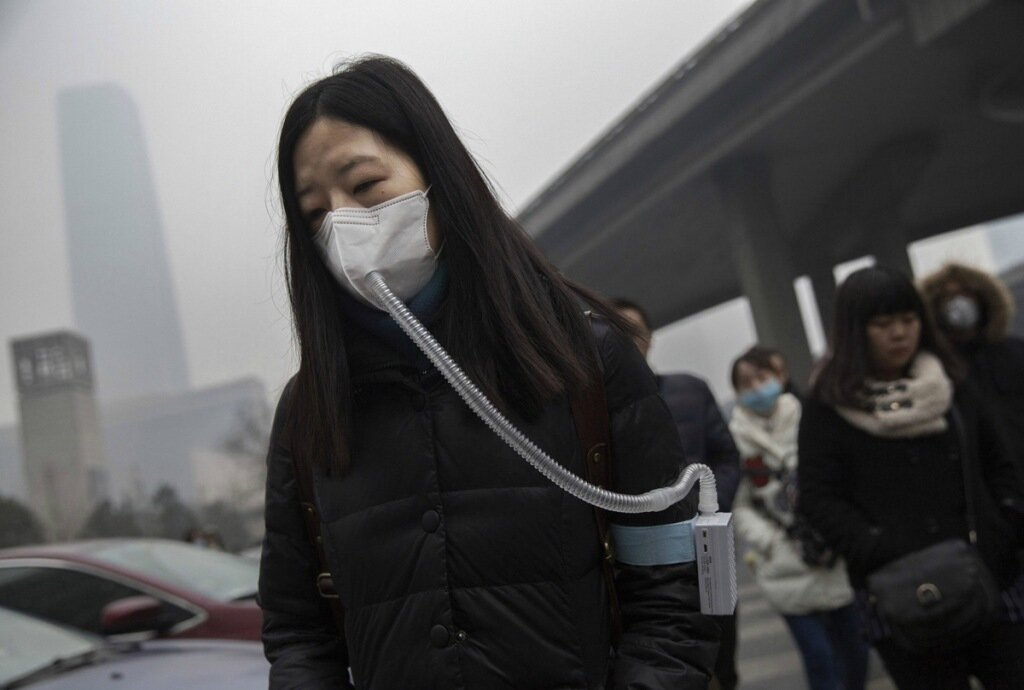 """BEIJING, CHINA - DECEMBER 09:  A  Chinese woman wears a mask and filter as she walks to work during heavy pollution on December 9, 2015 in Beijing, China. The Beijing government issued a """"red alert"""" Sunday for the first time since new standards were introduced earlier this year as the city and many parts of northern China were shrouded in heavy pollution. Levels of PM 2.5, considered the most hazardous, crossed 400 units in Beijing, lower then last week, but still nearly 20 times the acceptable standard set by the World Health Organization. The governments of more than 190 countries are meeting in Paris to set targets on reducing carbon emissions in an attempt to forge a new global agreement on climate change.  (Photo by Kevin Frayer/Getty Images)"""